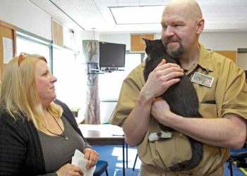 Inmate Kris Howe holds foster kitten Cecily while talking with Purrfect Paws Manager of Foster Care and Shelter Relocation Program Susan Bark during a celebration (fostercare@purrfectpals.org 206 719 6992) to commemorate the 500th cat to go through the Purrfect Pals Kitten Connection program at the Monroe Correction Complex in Monroe, Wash., Tuesday March 26, 2013. The program pair feral kittens with inmates help the kittens socialize and become adoptable.
